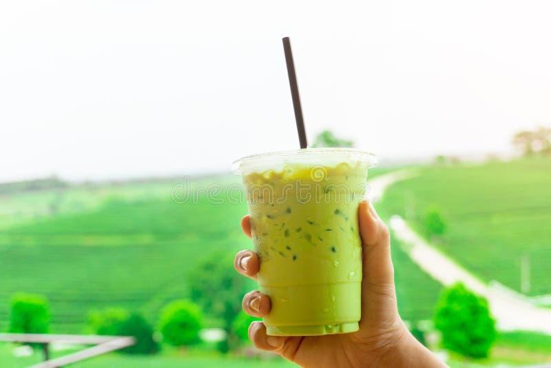 Sluit omhoog jonge Aziatische vrouwenhand houdend meeneem plastic kop van heerlijke bevroren groene thee of bevroren matcha op mo royalty-vrije stock afbeeldingen