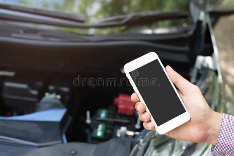 Sluit omhoog jonge bedrijfsmensenhand gebruikend een mobiele die smartphonevraag een autowerktuigkundige om hulphulp omdat auto v stock afbeelding