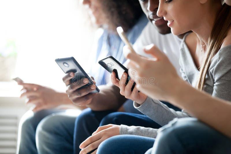 Sluit omhoog jonge gemengde rasmensen gebruikend telefoons royalty-vrije stock fotografie