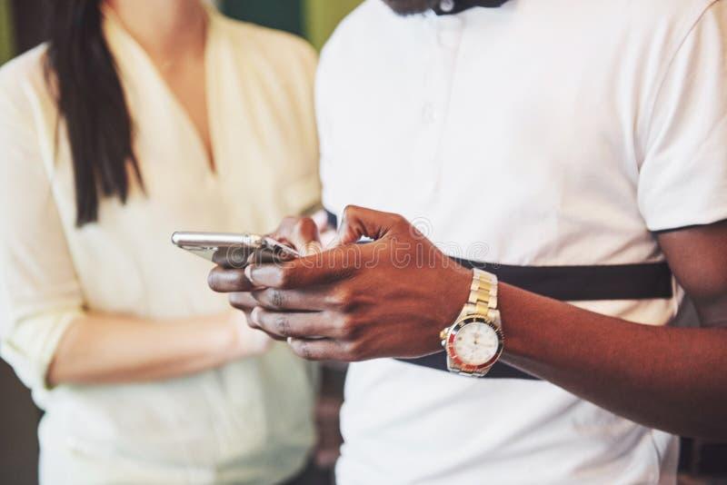 Sluit omhoog jonge vrienden die slimme telefoon bekijken terwijl het zitten in koffie Gemengde rasmensen in restaurant die mobiel stock fotografie
