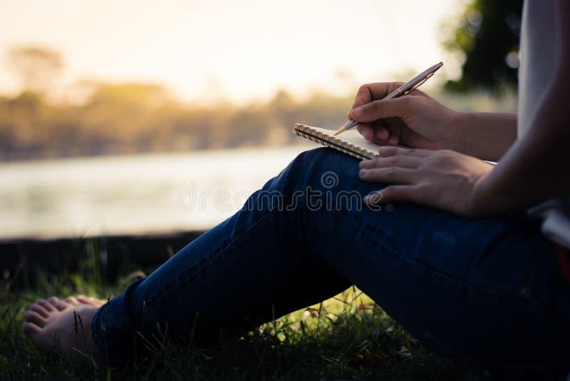 sluit omhoog jonge vrouwen die op notitieboekje in park, concept in edu schrijven royalty-vrije stock foto