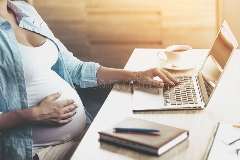 Sluit omhoog Jonge Zwangere Vrouw thuis Gebruikend Laptop stock fotografie