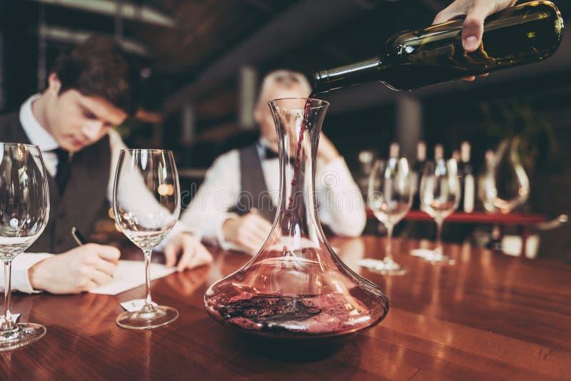 Sluit omhoog Kelners` s hand die rode wijn van fles gieten in karaf in restaurant Het proeven van de wijn royalty-vrije stock afbeelding