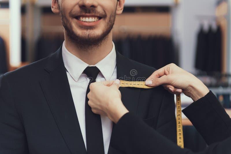 Sluit omhoog Kleermakersgebruik die band meten om afmetingen van klant te meten voor het maken van kostuum royalty-vrije stock afbeelding