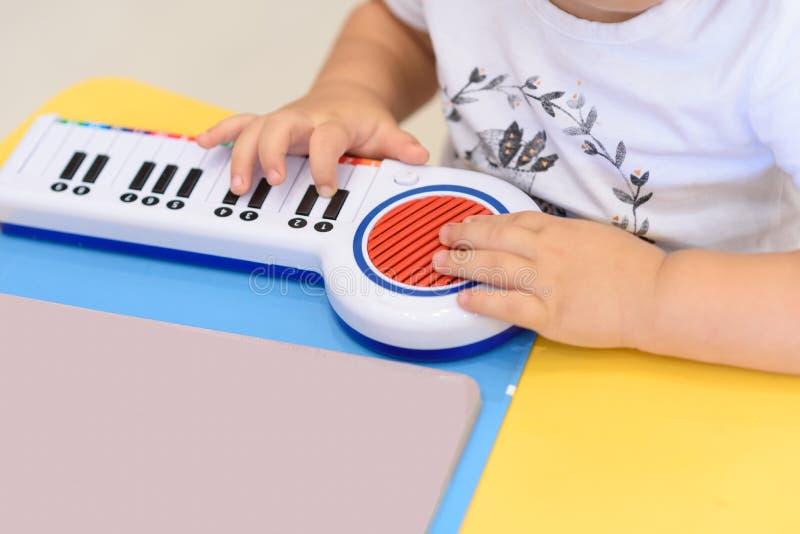 Sluit omhoog kleine handenspelen op een stuk speelgoed piano stock afbeelding