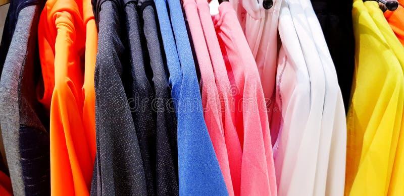 Sluit omhoog kleurrijk lang kokeroverhemd op hanger bij de winkel van de mensenmanier stock fotografie