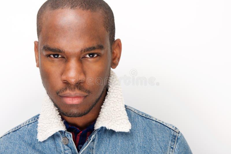 Sluit omhoog koele jonge Afrikaanse Amerikaanse mannelijke mannequin starend door witte muur stock fotografie