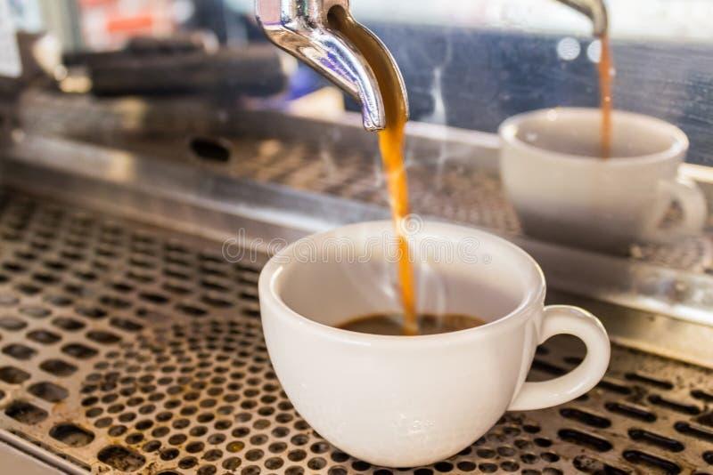 Sluit omhoog Koffiemachine makend espresso in een koffie stock foto's