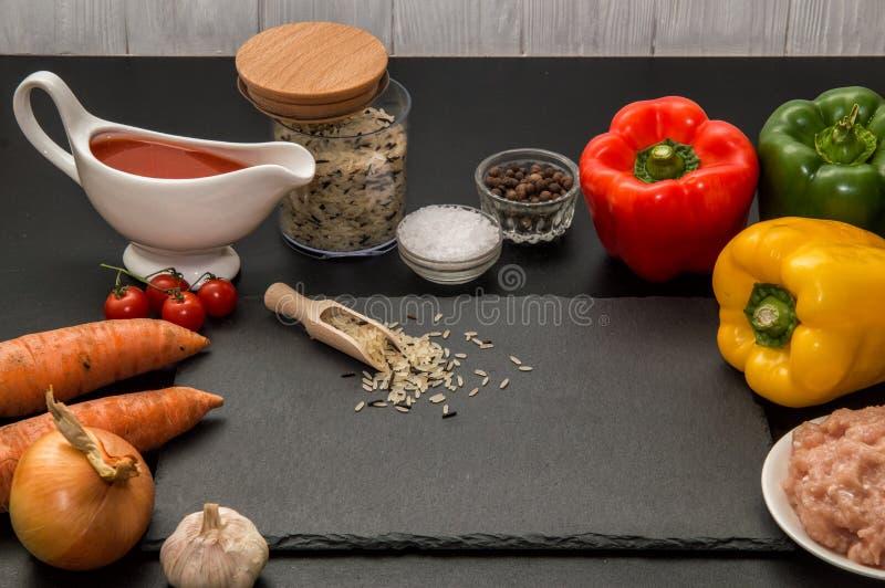 Sluit omhoog Kokend diner thuis Ingrediënten voor het roosteren van gevulde groene paprika's Zwarte achtergrond royalty-vrije stock afbeelding