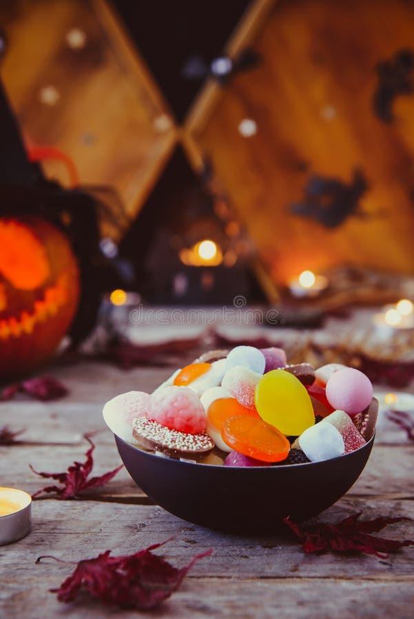 Sluit omhoog kom met suikergoed en gesneden pompoen in heksenhoed met document silhouetten van knuppels, kasteel, spoken op houte royalty-vrije stock afbeelding