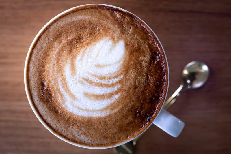 Sluit omhoog kop van lattekoffie met wit schuim op houten lijst royalty-vrije stock afbeelding