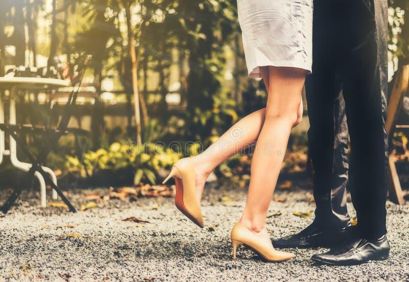 Sluit omhoog kussend paar in het park met een warm ochtendlicht stock foto