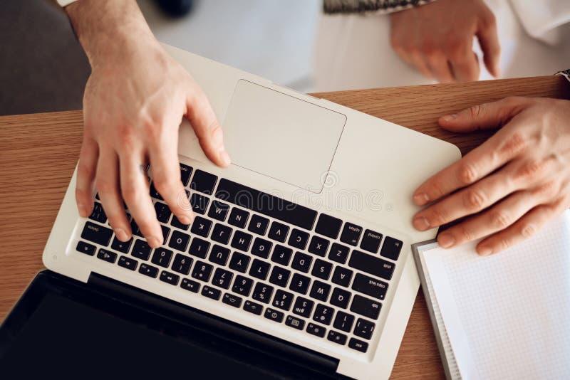 Sluit omhoog laptop op de lijst met drie handen stock foto