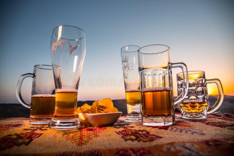 Sluit omhoog lege mokken bier op een zonsopgangachtergrond met bergen De bierpartij is over concept royalty-vrije stock fotografie