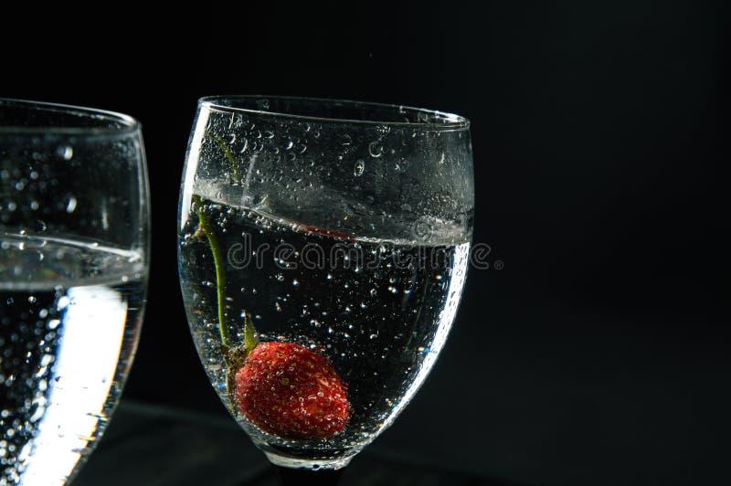 Sluit omhoog, macro Het glas wordt gevuld met het sissen van wijn Bij de bodem van de bes is behandeld met bellen De ruimte van h royalty-vrije stock foto
