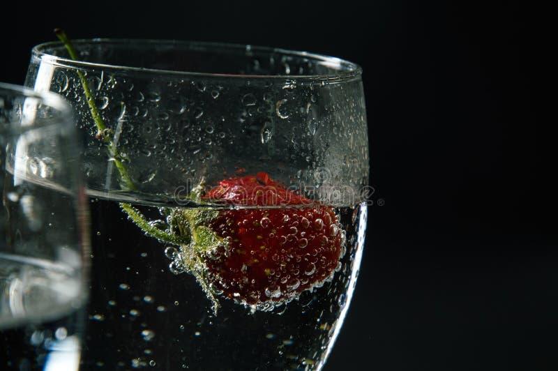 Sluit omhoog, macro Rode aardbei in een alcoholische drank met bellen Ge?soleerde op zwarte achtergrond stock foto's