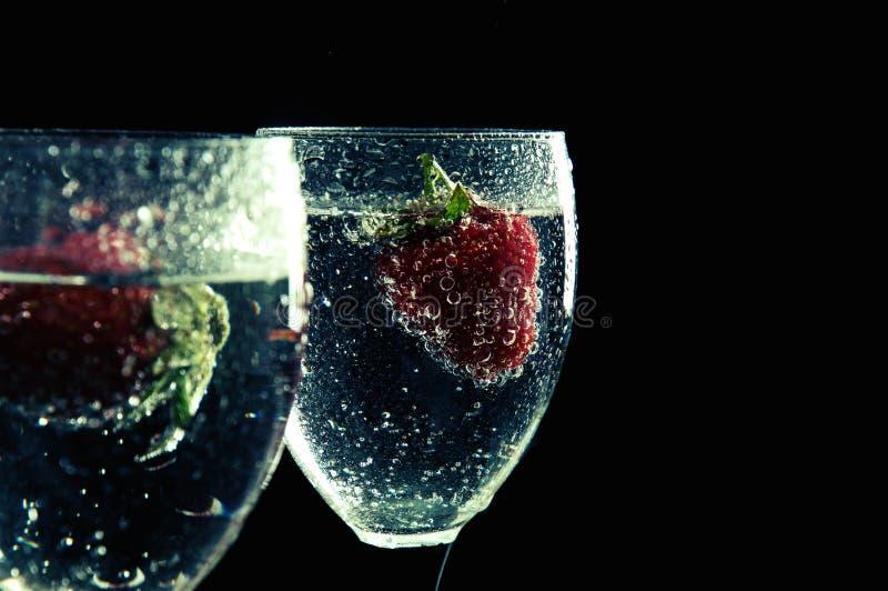 Sluit omhoog, macro Wijnglazen met Fonkelende Drank worden gevuld die Binnenaardbei Ge?soleerde op zwarte achtergrond stock fotografie