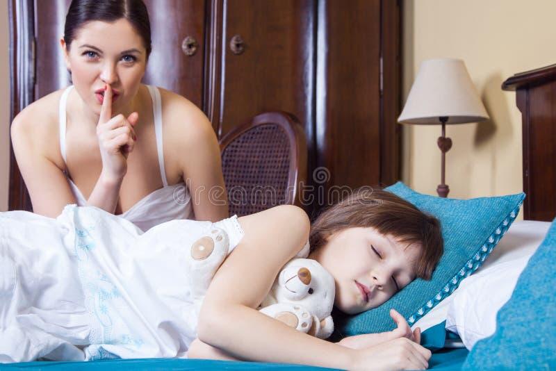 Sluit omhoog mamma en dochter in slaapkamer Moeder die knoeiboelteken a tonen stock afbeeldingen