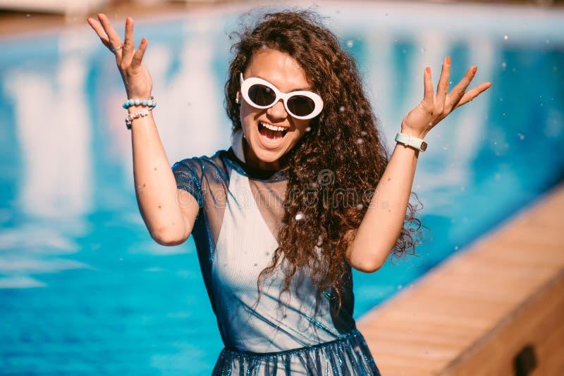 Sluit omhoog manierportret van het sensuele het glimlachen schoonheids donkerbruine vrouw stellen in zwembad, geniet het ontspann royalty-vrije stock afbeeldingen