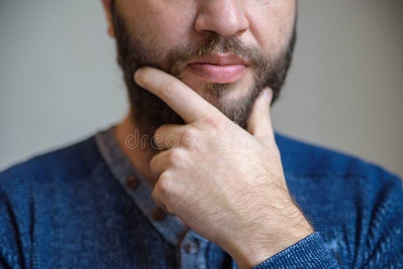 Sluit omhoog mannelijke handaanrakingen zijn baard stock foto's