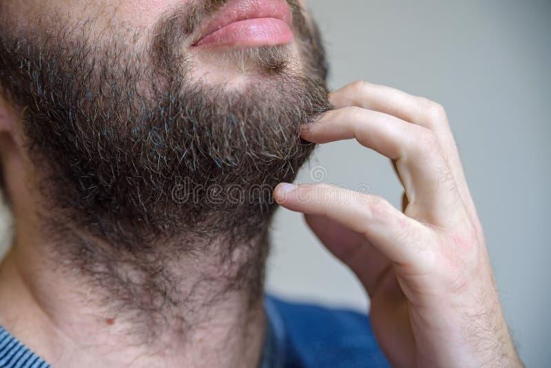 Sluit omhoog mannelijke handaanrakingen zijn baard royalty-vrije stock foto