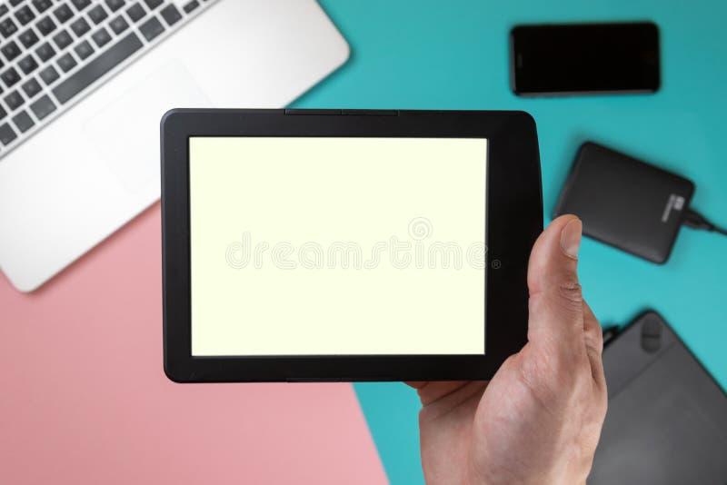 Sluit omhoog mannelijke handen houdend een tablet op de achtergrond van de bureaulijst royalty-vrije stock afbeelding