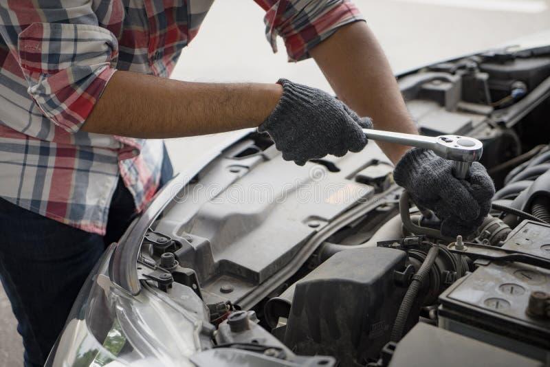 Sluit omhoog mechanische mensen vuile handen gebruikend hulpmiddel om reparatieauto te bevestigen stock foto's