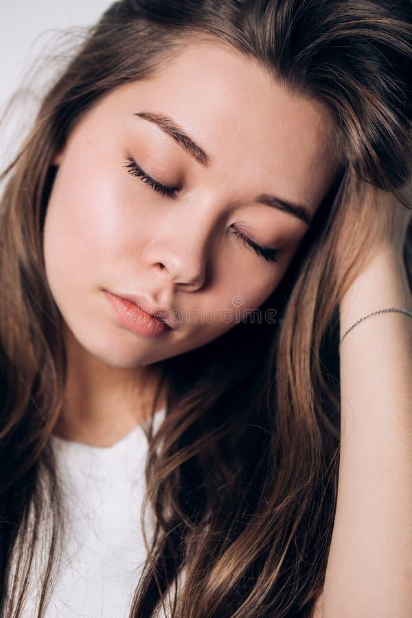 Sluit omhoog meisje in sweater dichtbij het venster Gesloten ogen Tederheid, ontspanning stock fotografie