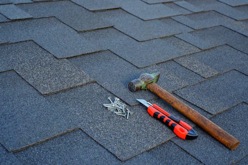 Sluit omhoog mening over asfaltdakspanen op een dak met hamer, spijkers en de achtergrond van het kantoorbehoeftenmes royalty-vrije stock foto