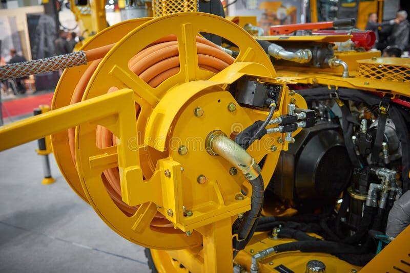 Sluit omhoog mening over de nieuwe gele machine van de luchtcompressor voor mijnbouw op tentoonstellingstribune Trommel met rubbe stock afbeeldingen