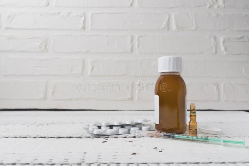 Sluit omhoog mening over een witte houten lijst met verschillende geneesmiddelen en spuit Griep en seizoengebonden ziekten inenti royalty-vrije stock foto