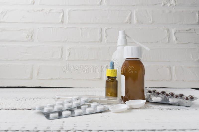 Sluit omhoog mening over een witte houten lijst met verschillende geneesmiddelen Griep en seizoengebonden ziekten Het concept van stock afbeelding