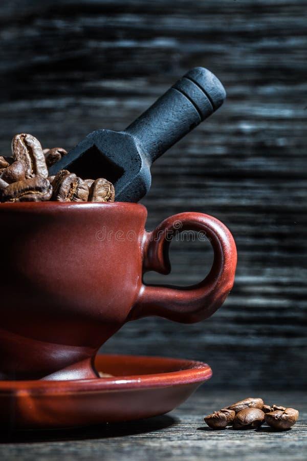 Sluit omhoog mening over kop met koffiebonen en lepel stock afbeeldingen