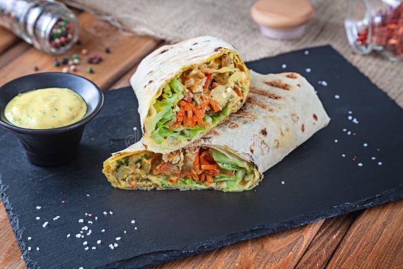 Sluit omhoog mening over Shawarma-sandwich, gyroscoop vers broodje in lavash Shaurma op zwarte steen wordt gediend die Kebab in p stock foto