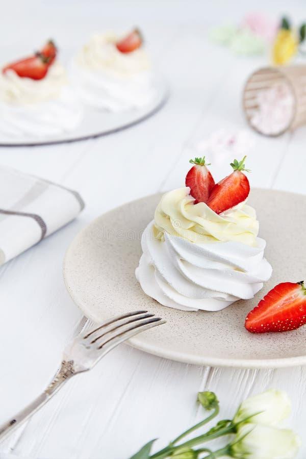 Sluit omhoog mening over smakelijk Pavlova-cakedessert met aardbei op witte houten achtergrond Heerlijk traditioneel Australisch  stock foto's