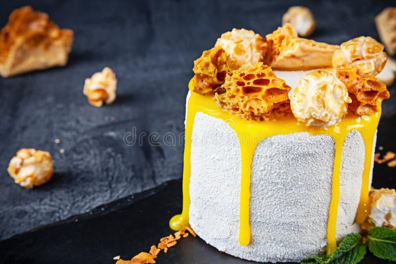 Sluit omhoog mening over smakelijke witte cake met honing, karamel en koekje Dessert dat op donkere achtergrond met exemplaarruim royalty-vrije stock foto's