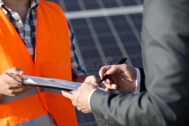 Sluit omhoog mening over voorman en cliënt sigining contract bij zonnekrachtcentrale royalty-vrije stock foto