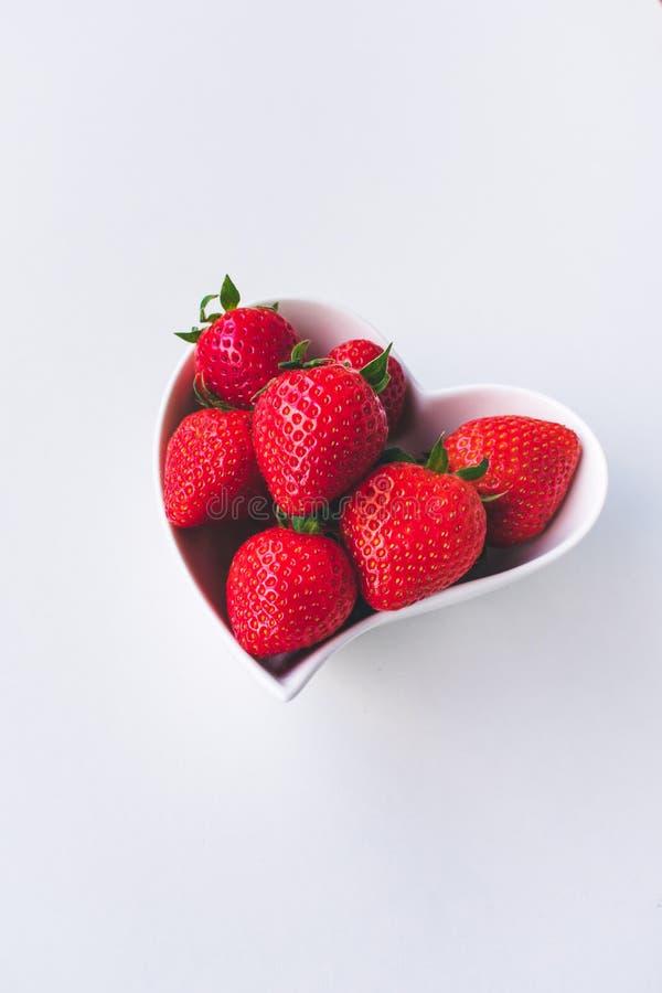 Sluit omhoog mening van aardbeien in een witte hart gevormde kom op witte achtergrond royalty-vrije stock fotografie