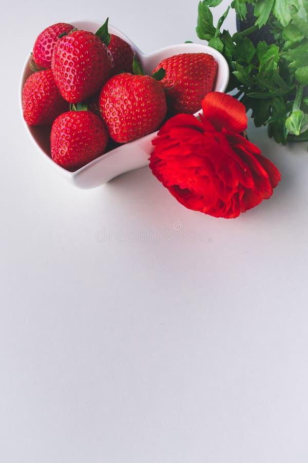 Sluit omhoog mening van aardbeien en een rode bloem in een witte hart gevormde kom op witte achtergrond royalty-vrije stock foto's