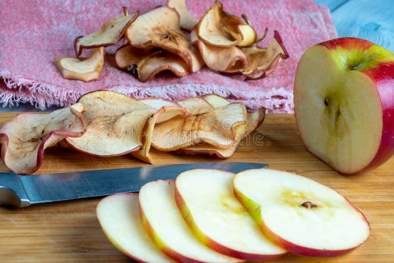 Sluit omhoog mening van appelspaanders en vers-besnoeiingsappel met het mes op een houten achtergrond Zachte nadruk stock afbeeldingen