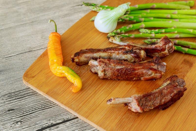 Sluit omhoog mening van barbecueribben met gebraden gerechten en op een oude houten lijst royalty-vrije stock afbeelding