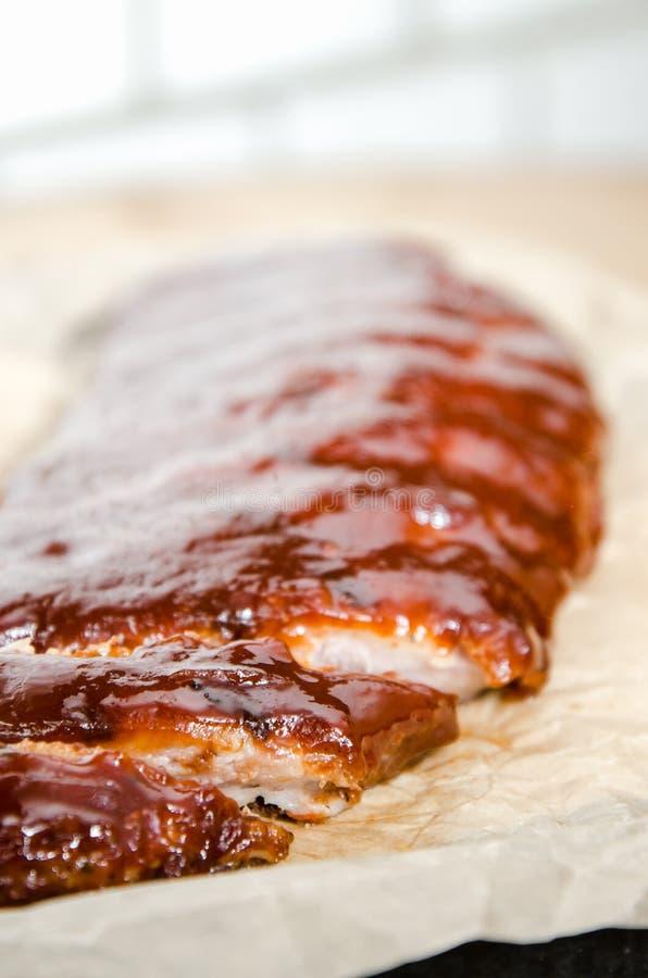 Sluit omhoog mening van barbecueribben met gebraden gerechten en saus op een oude houten lijst stock fotografie