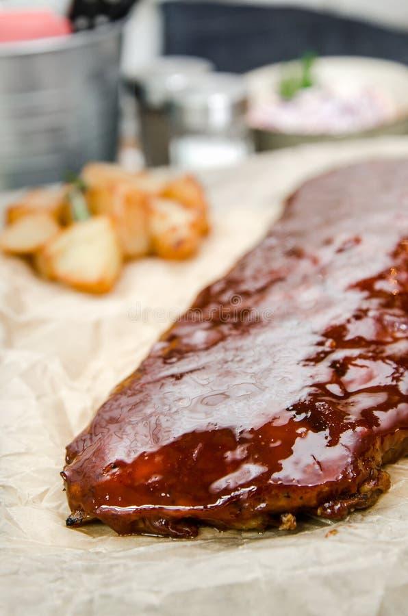 Sluit omhoog mening van barbecueribben met gebraden gerechten en saus op een oude houten lijst stock afbeelding