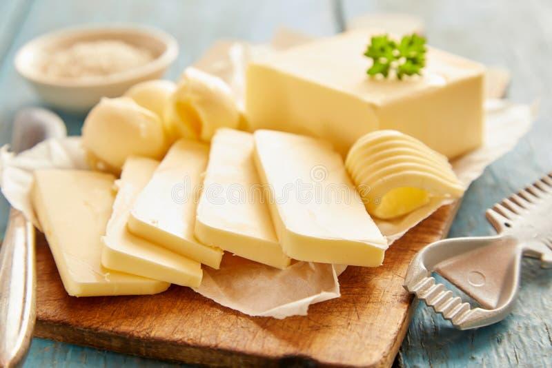 Sluit omhoog mening van boter op scherpe raad wordt gesneden die royalty-vrije stock foto's