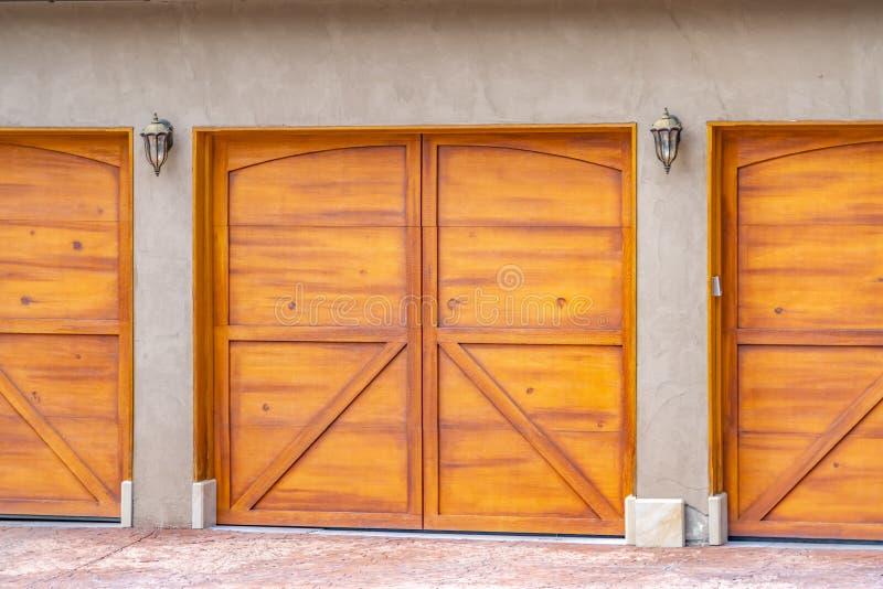 Sluit omhoog mening van de bruine houten garagedeur bij de buitenkant van een huis stock afbeeldingen