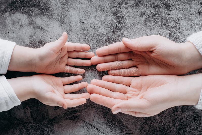 Sluit omhoog mening van de handen van de familieholding, houdend van gevend moeder ondersteunend kind Het helpen van hand en hoop stock fotografie