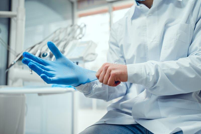 Sluit omhoog mening van de handen van de mannelijke arts zettend op blauwe gesteriliseerde chirurgische handschoenen in de medisc royalty-vrije stock afbeelding