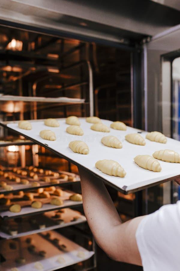 Sluit omhoog mening van de holdingsrek van de vrouwenholding van croissants in een bakkerij stock afbeelding