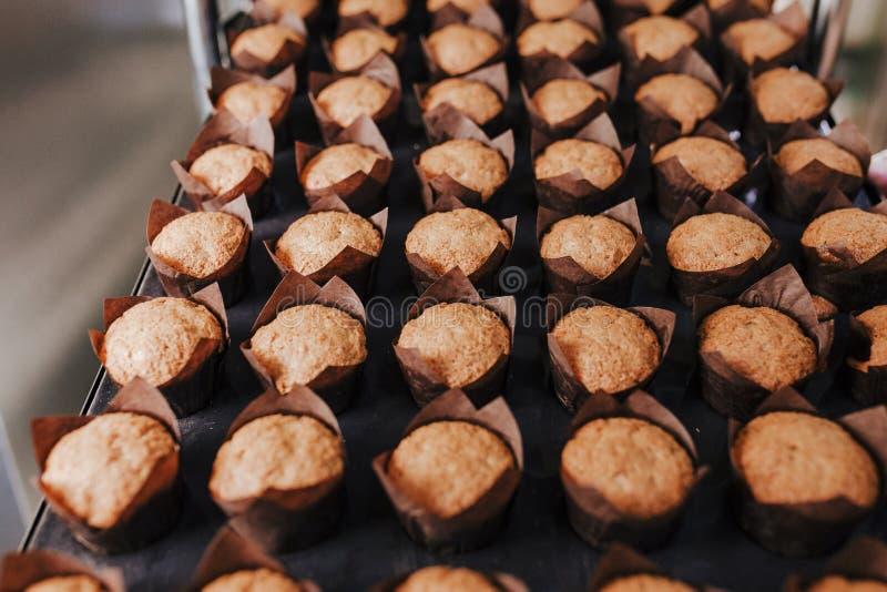 Sluit omhoog mening van de holdingsrek van de vrouwenholding van croissants in een bakkerij royalty-vrije stock fotografie