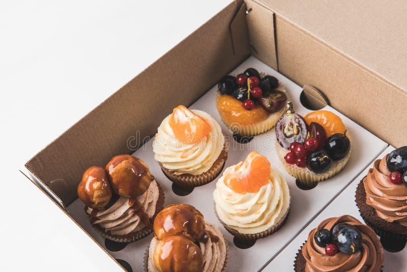 Sluit omhoog mening van diverse types van cupcakes in kartondoos stock foto's